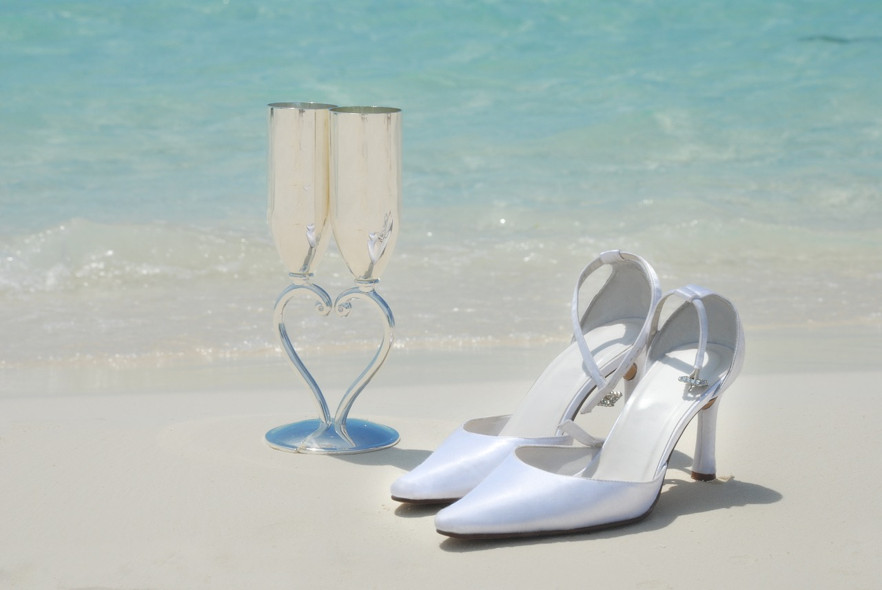 Wedding Shoes And Champagne Glasses On The Beach